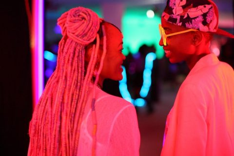 A still from Rafiki. Two people gaze at each other lit by pink light. The person on the left has long braided hair. The person on the right wears sunglasses and a backwards cap.