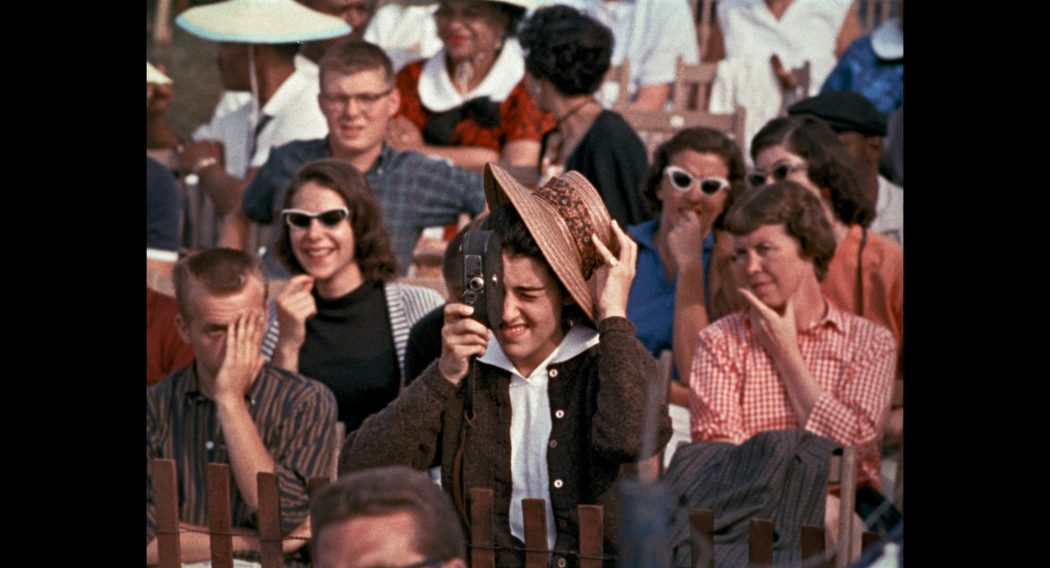 Woman with a movie camera in a crowd